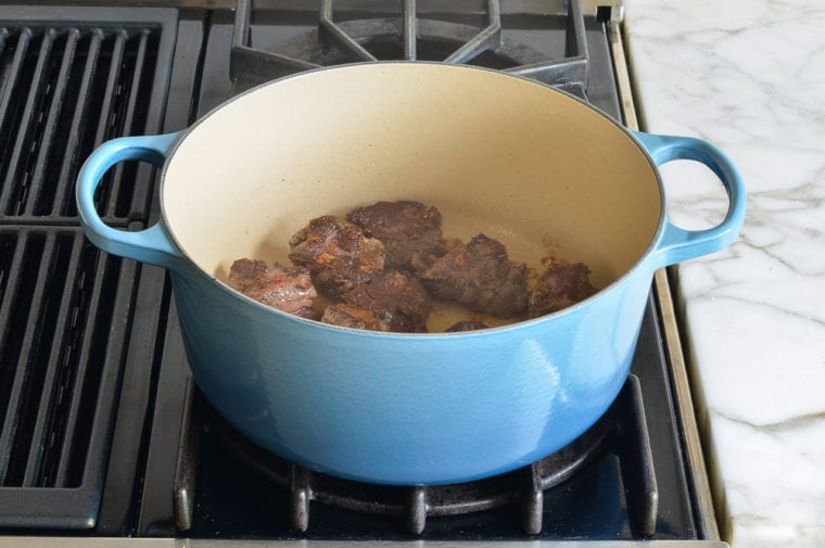 Lấy thịt ra và thêm hành tây, tỏi và giấm balsamic vào chảo. Giấm sẽ nới lỏng tất cả các bit màu nâu từ đáy chảo và thêm hương vị.